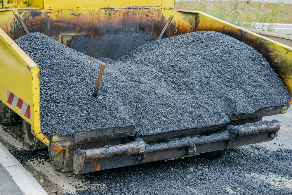 Back View Of A Large Asphalt Paving Machine Full Of Fresh Asphalt.