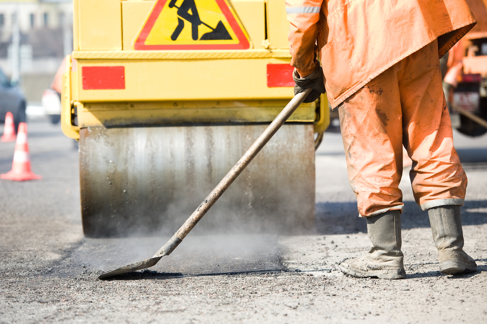 Builder With Shovel At Asphalting Process  During Road Street Repairing Works